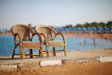 Two single chairs are on the beach