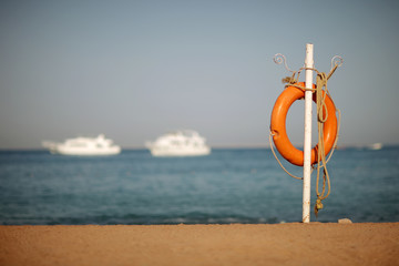 Lifebuoy and rope on the sea shore