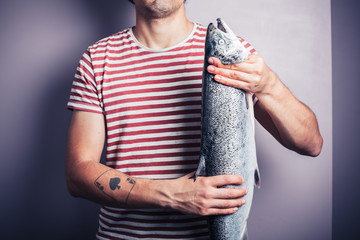 Young man posing with a salmon