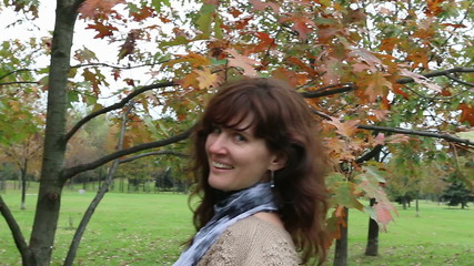 Happy woman walking in autumn park