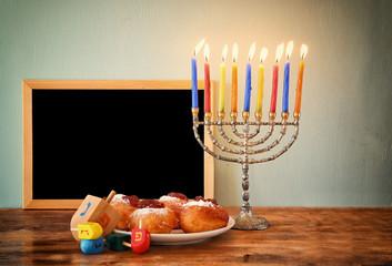 jewish holiday Hanukkah with menorah, doughnuts over wooden tabl