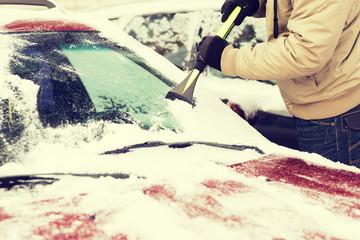 closeup of man scraping ice from car