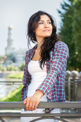 Girl in plaid shirt looking over her shoulder toward the sky