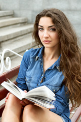 Girl of twenty reads a book while sitting on a bench