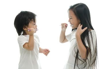 Little  asian girl and boy brushing teeth