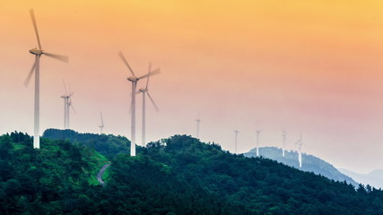 Timelapse of a wind mill farm in the mountains at sunset