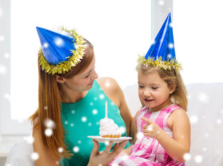 mother and daughter in party hats with cake
