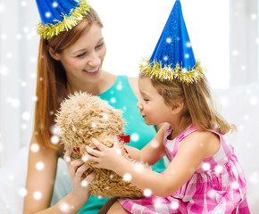 mother and daughter in party hats with toy