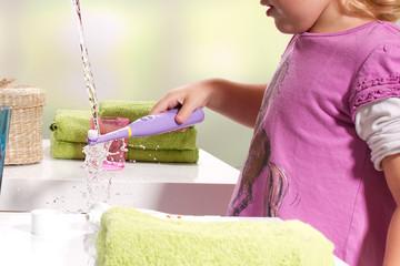 Mädchen reinigt ihre elektrische Zahnbürste