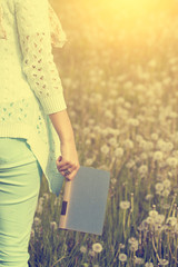 Woman standing in dandelion field with a book