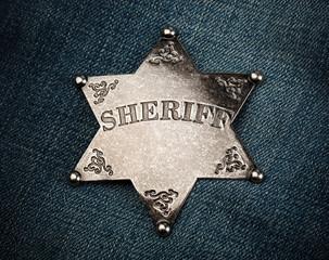 Sheriff star badge on blue denim background