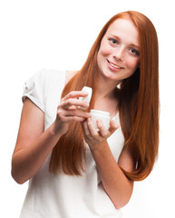 Young red-haired girl holding a package with a face cream. Isola