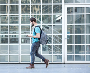 Male student walking on campus with bag and mobile phone