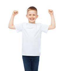 little boy in blank white t-shirt showing muscles