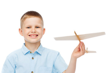 smiling little boy holding a wooden airplane model