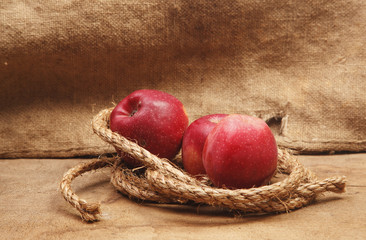Red apples on the background burlap and wooden board