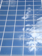 Blue glass facade reflecting white cloud