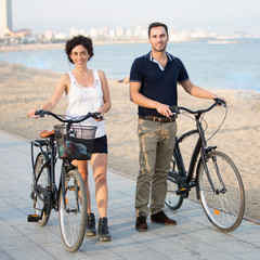 Tourists with rented bikes walking