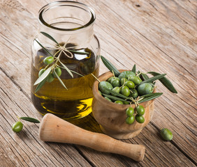 Jar of olive oil with olive branch in a  mortar