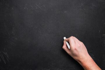 Hand mit Kreide vor einer Kreidetafel