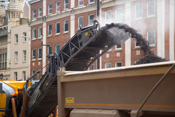 Construction workers operate a cold milling machine.