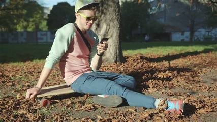 Handsome boy in autumn park with a skateboard texting on phone