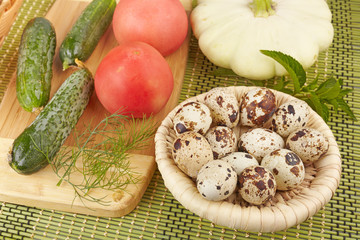 Vegetables and quail eggs in a basket on a green background