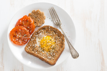 fried egg in toast, grilled tomatoes for breakfast on a plate