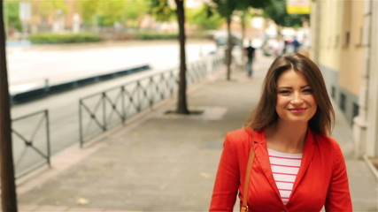 Woman walking on the street and smiling, steadycam shot