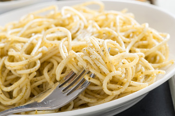 plate of spaghetti with pesto and cheese, close-up