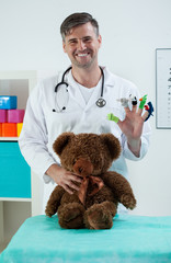 Smiling pediatrician in his office