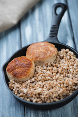 Frying pan with buckwheat and meat cutlets, studio shot