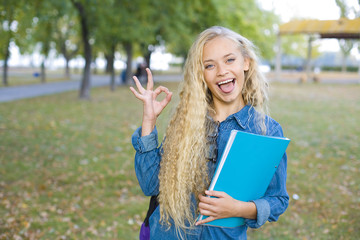 Beautiful student showing OK sign