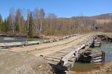 Wooden bridge over the turbulent river