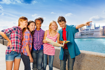 Kids with map standing together on embankment