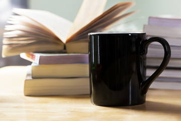 black coffee cup and book pile