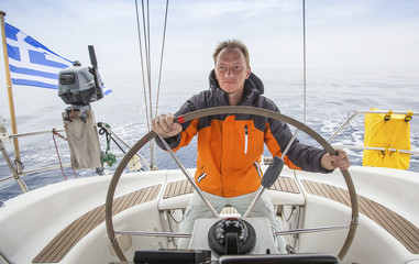 Young man sailing in the Sea. Yacht skipper. Sailing.