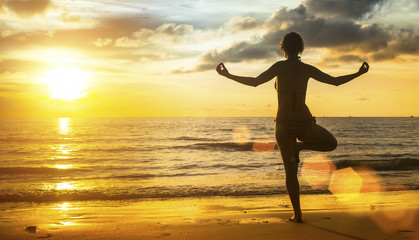 Yoga woman silhouette meditation on the beach at sunset.