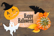 Old paper with Halloween decorations on wooden background