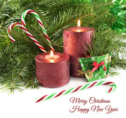 Two red candles with natural conifer and canes