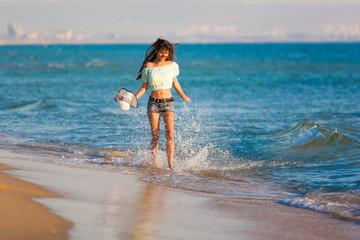 brunette woman run sea in jeans shorts