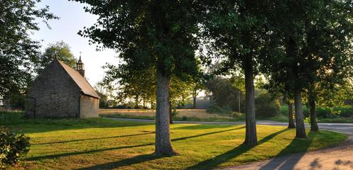 Chapelle isolée entourée d'arbres avec du soleil