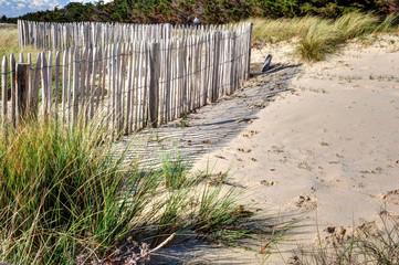 Barrière de bois dans les dunes et ombres sur le sable