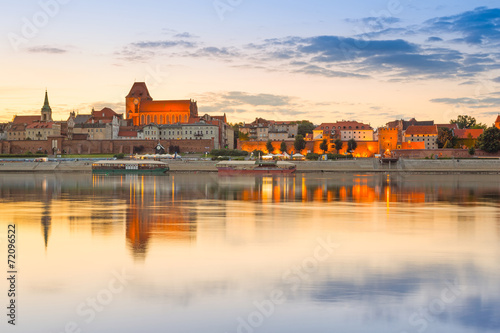 Fototapeta Torun old town reflected in Vistula river at sunset, Poland