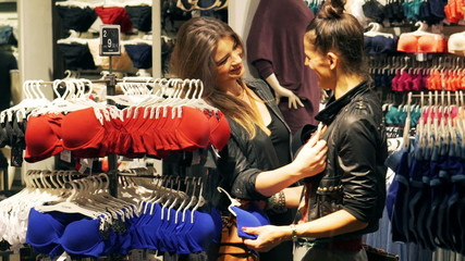 Female friends shopping in the shop with underwear, steadycam