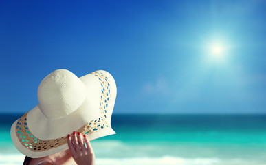 woman wearing hat and sunny beach