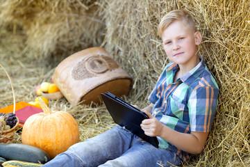 Мальчик с планшетом на сеновале