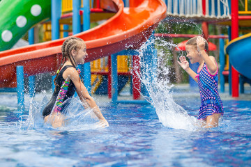 two little kids playing in the swimming pool