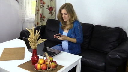 pregnant woman sit at table work with computer and talk on phone