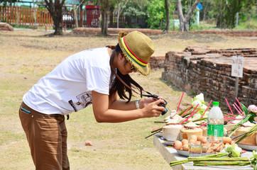 Thai women photographer shooting Sacrificial offering at Ruins